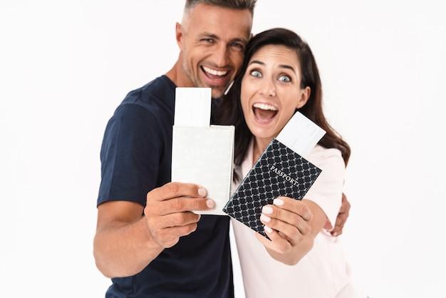 Fröhliches attraktives paar in lässigem outfit, das isoliert über weißer wand steht und pässe mit flugtickets zeigt