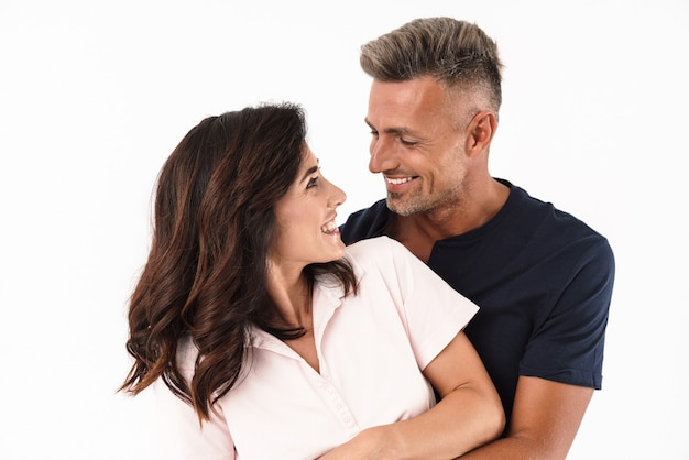 Fröhliches attraktives verliebtes paar in lässigem outfit, das isoliert über weißer wand steht und sich umarmt