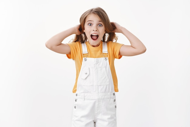 Fröhliches aufgeregtes kind, das spaß hat, verspielt und überrascht steht, mädchen berührt die haare, hebt den haarschnitt in die luft, schreit amüsiert und fröhlich, drückt begeistert fröhliche stimmung aus, steht weiße wand