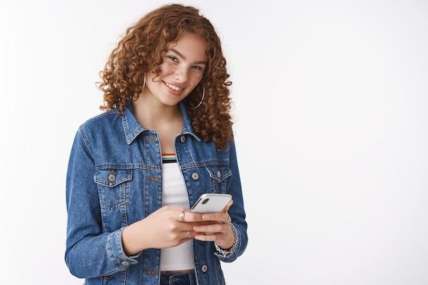 Fröhliches ausgehendes stilvolles ingwer-jugendmädchen mit lockigen pickeln, das smartphone spielt, das telefonspiel spielt, verwenden eine lustige app, die sie hinterhältig freudig lächelnd nachrichten spricht, die sie gleichzeitig sprechen