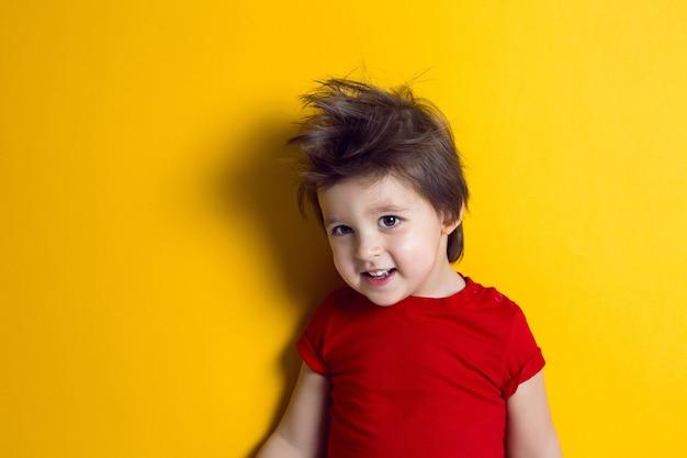 Fröhliches baby im roten t-shirt steht auf gelbem hintergrund