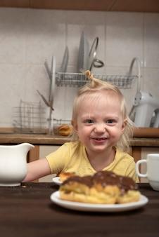 Fröhliches blondes kind in der küche frühstückt und betrachtet die kuchen. kleines mädchen, das tee mit süßigkeiten trinkt.