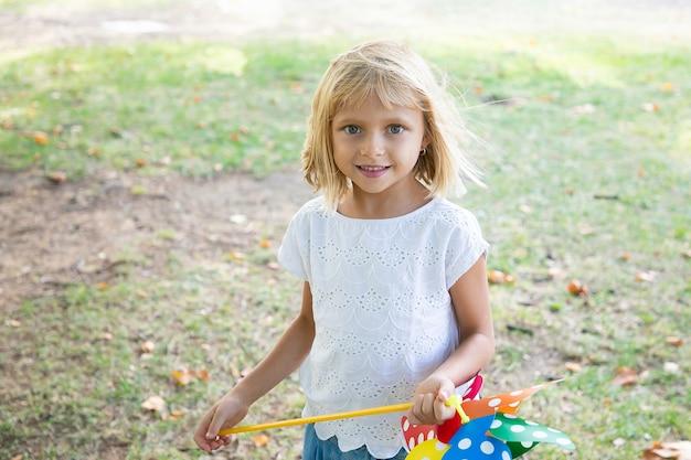 Fröhliches blondes mädchen, das im park spielt, windrad hält und lächelt. vorderansicht. outdoor-aktivitätskonzept für kinder