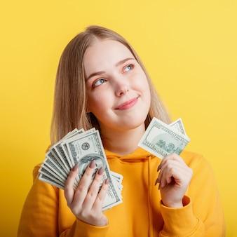 Fröhliches blondes mädchen im teenageralter, das in händen geld-bargeld-dollar hält und nachdenklich auf gelbem hintergrund träumt. junge aufgeregte lächelnde frau des porträts stapel geldbanknoten. nahaufnahmequadrat.