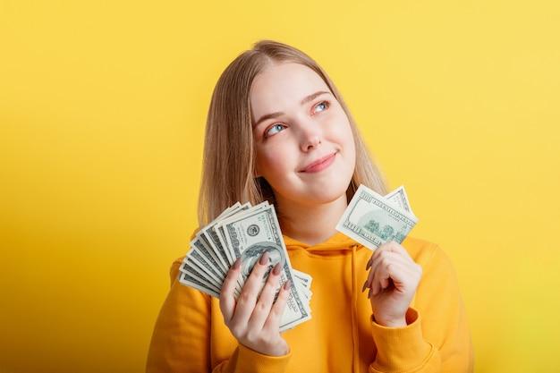 Fröhliches blondes mädchen im teenageralter, das in händen geld-bargeld-dollar hält und nachdenklich auf gelbem hintergrund träumt. junge aufgeregte lächelnde frau des porträts stapel geldbanknoten.