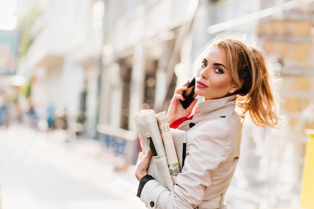 Fröhliches blondes mädchen mit hellem make-up, das papier und laptop trägt, die vom büro nach hause zurückkehren