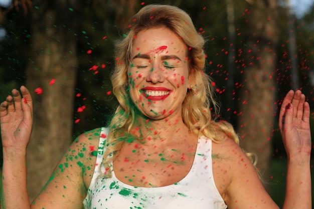 Fröhliches blondes model trägt weißes hemd und posiert mit trockener farbe bedeckt beim holi-festival