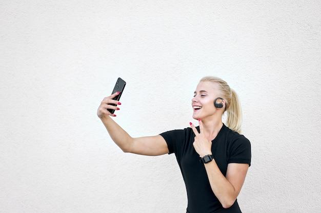 Fröhliches blondes sportliches mädchen, das sanft lächelnd schwarze sportbekleidung trägt, die musik hört, selfi nimmt und singenden sieg zeigt.