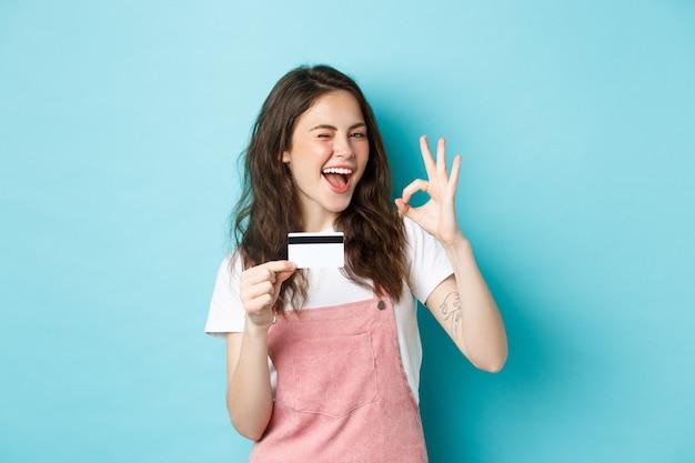 Fröhliches brünettes mädchen, das plastikkreditkarte und okayzeichen zeigt, zwinkert und selbstbewusst lächelt, logo empfehlen, auf blauem hintergrund stehend