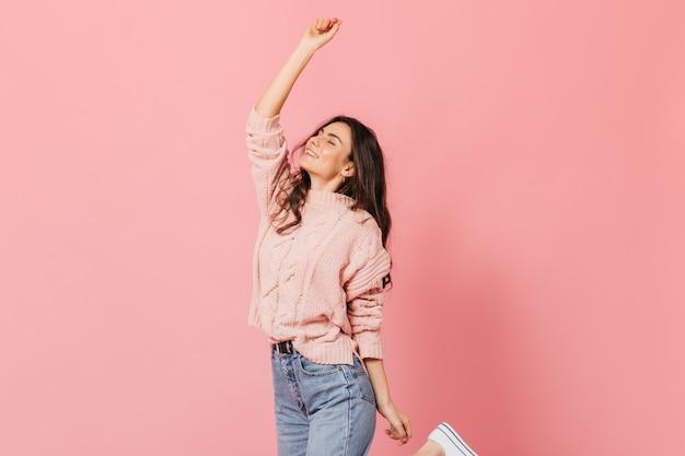 Fröhliches brünettes mädchen im gestrickten pullover und in den blauen jeans hebt ihre hand und lächelt auf rosa hintergrund.