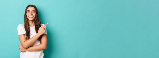 Fröhliches brünettes mädchen im weißen t-shirt lächelt zufrieden und zeigt mit dem finger auf die obere rechte ecke...