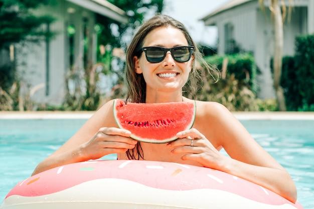 Fröhliches brünettes mädchen in einem schwarzen bikini, der eine wassermelone in ihren händen hält und lächelt