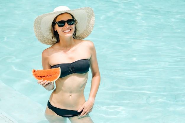 Fröhliches brünettes mädchen in einem schwarzen bikini im pool am hotel, das eine wassermelone in ihren händen hält und lächelt