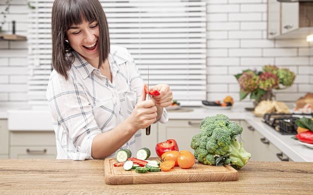 Fröhliches brünettes mädchen schneidet gemüse auf salat auf dem hintergrund des modernen kücheninnenraums.