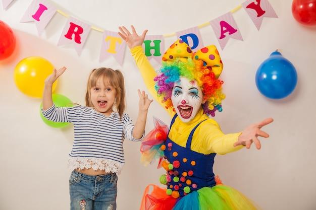 Fröhliches clownmädchen im urlaub spielt mit dem geburtstagskind