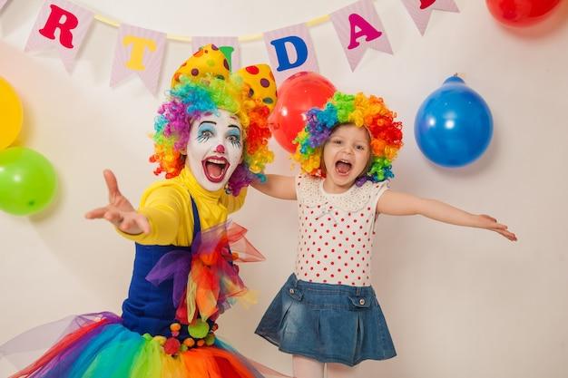 Fröhliches clownmädchen im urlaub zeigt emotionen mit dem geburtstagskind