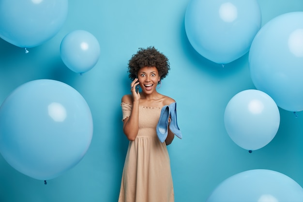 Fröhliches dunkelhäutiges weibliches model hält modische schuhe auf high heels, hat telefongespräch, trägt beige kleid, models in blauer wand, luftballons herum. stil- und kleidungskonzept