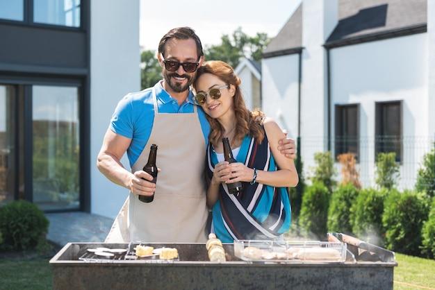 Fröhliches ehepaar, das fleisch grillt, während bär zusammen trinkt