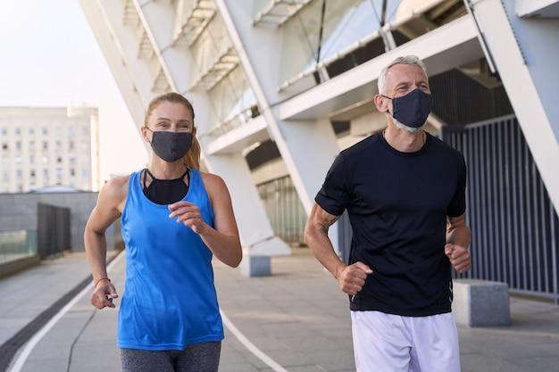 Fröhliches ehepaar mittleren alters, das gesichtsschutzmasken trägt, die in der städtischen umgebung zusammenlaufen