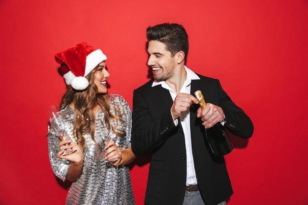 Fröhliches, elegant gekleidetes paar, das isoliert über dem roten raum steht und neujahr feiert
