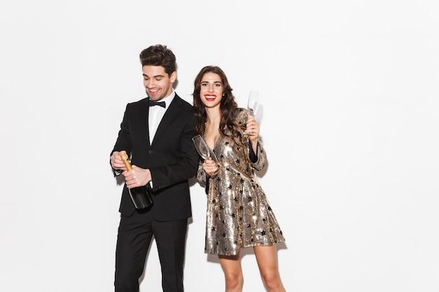 Fröhliches, elegant gekleidetes paar, das isoliert über weiß steht und neujahr feiert und champagner trinkt