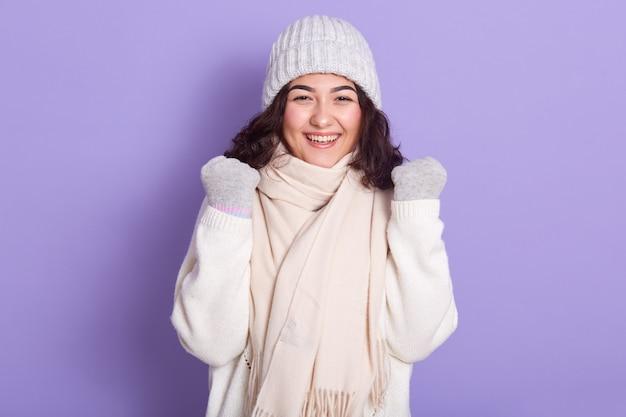 Fröhliches, entzückendes junges model, das ihre fäuste hebt, in hochstimmung ist, lacht, kaltes wetter liebt