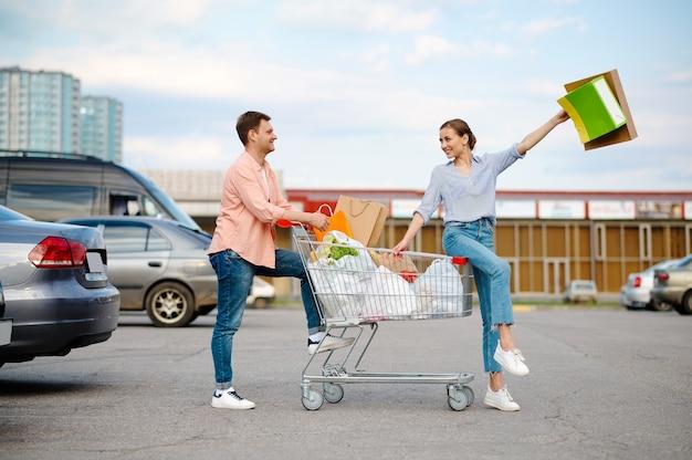 Fröhliches familienpaar mit taschen im warenkorb auf dem parkplatz des supermarkts. zufriedene kunden mit einkäufen aus dem einkaufszentrum, fahrzeugen