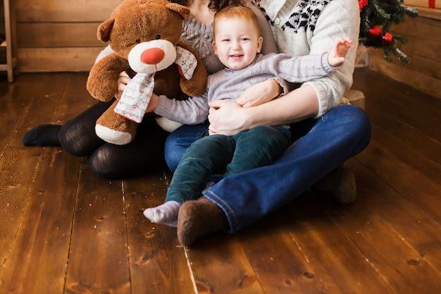 Fröhliches familienporträt zu weihnachten, mutter, vater und sohn, die zu hause auf einem hochstuhl sitzen, weihnachtsdekoration und geschenke um sie herum