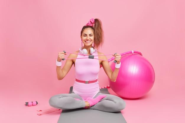 Fröhliches fitness-frauenmodell sitzt gekreuzte beine auf matte dehnt expander trainiert muskeln im body, umgeben von schweizer ballwiderstandsband hula hoop macht übungen zum abnehmen.