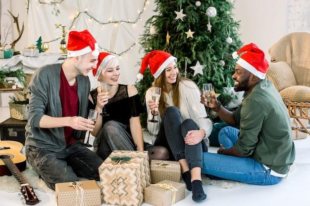 Fröhliches foto von vier freunden, die auf weihnachtsfeier mit champagner lachen