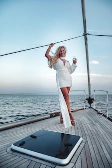 Fröhliches frauenporträt im mittleren alter auf dem deck einer segelyacht, die eine wasserreise auf einer küstenkreuzfahrt im sommer genießt. weibliche geschäftsfrau auf segelboot während des sonnenuntergangs. konzept reiseabenteuer, segeln und urlaub