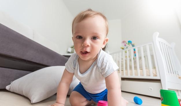 Fröhliches, fröhliches baby, das auf dem boden spielt und in die kamera schaut