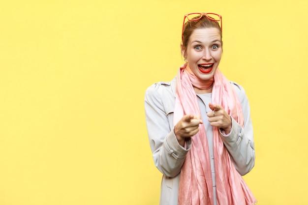 Fröhliches fröhliches mädchen mit mantel rosa schal rote brille, das mit den fingern auf die kamera schaut und zeigt