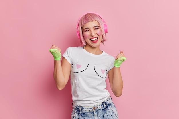Fröhliches, fröhliches teenager-mädchen macht ja-geste, ballt fäuste und ruft glücklich aus, fühlt sich wie ein gewinner in freizeitkleidung hat eine rosa bob-frisur hört musik über drahtlose kopfhörer posiert drinnen