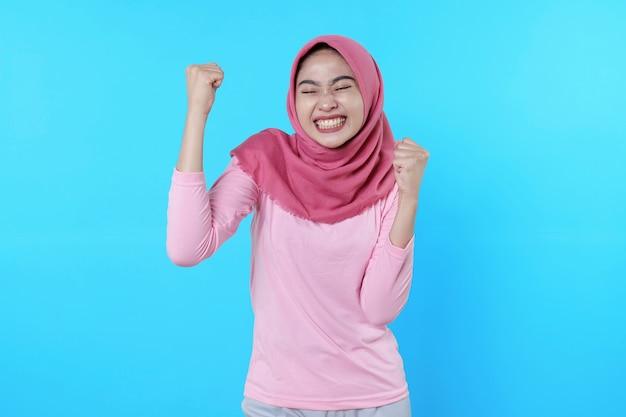 Fröhliches, fröhliches tragen von hijab und rosa t-shirt erzielen ein gutes ergebnis und lächeln im großen und ganzen in bester stimmung