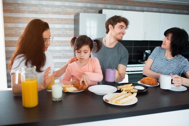 Fröhliches frühstück einer großen familie in der küche. geschwister, eltern und kinder, mutter und großmutter. vater und tochter. jeder isst morgens und plaudert und hat spaß.