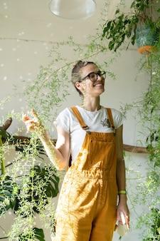Fröhliches gärtnermädchen in hausgartenfloristin genießt die pflege von zimmerpflanzen im gewächshaus