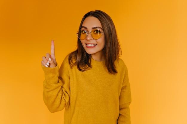 Fröhliches gebräuntes mädchen in den gläsern, die auf orange wand aufwerfen. ansprechende junge dame im strickpullover herumalbern.