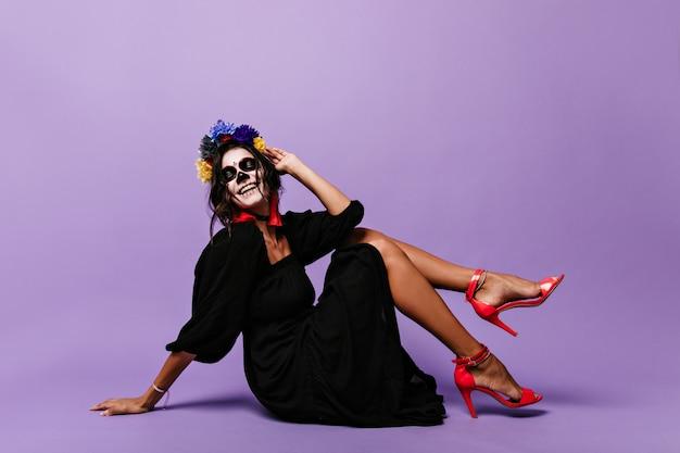 Fröhliches gebräuntes modell im schwarzen kleid, das auf boden aufwirft. flirtende frau mit gemaltem gesicht lacht von ganzem herzen.
