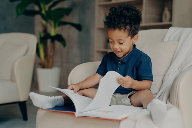 Fröhliches gemischtes kind mit süßem lockigem haar, das zu hause ein buch liest