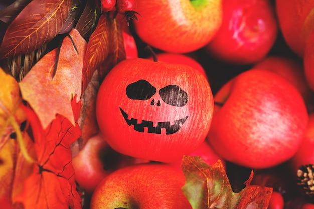 Fröhliches gesicht gemalt an einem apfel-halloween-urlaub
