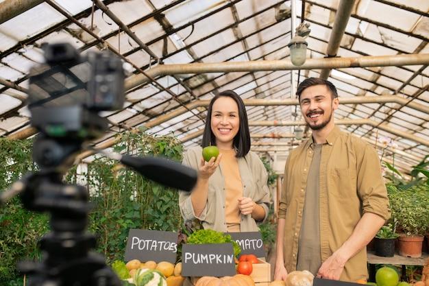 Fröhliches gesundes junges paar, das mit gemüse am tisch steht und über den nutzen von bio-lebensmitteln erzählt, während video schießt