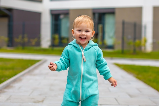Fröhliches, gesundes, schönes baby in blauem overall, das spaß in der stadt hat, aktives kind an einem kalten tag im freien