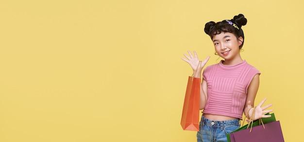 Fröhliches, glückliches asiatisches kind, das das einkaufen genießt, trägt sie einkaufstaschen im einkaufszentrum. panorama-