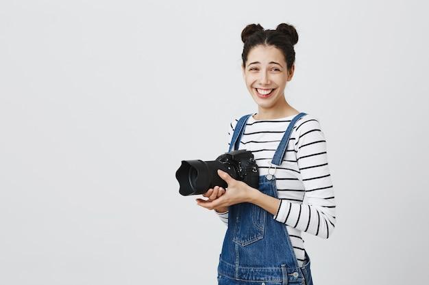 Fröhliches glückliches hipster-mädchen, das fotos macht, lacht und kamera benutzt, fotografiert