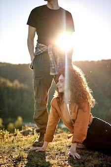 Fröhliches glückliches junges kaukasisches paar, das während des abenteuers in der landschaft rothaarige lockige frauen eine pause macht...