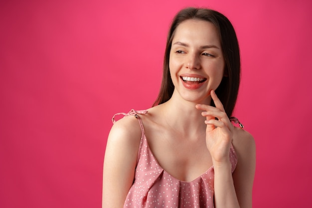 Fröhliches glückliches junges schönes mädchen, das gegen rosa hintergrund lächelt und lacht
