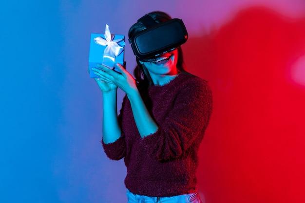 Fröhliches glückliches mädchen, das eine vr-virtual-reality-brille trägt und eine geschenkbox in der nähe des ohrs hält