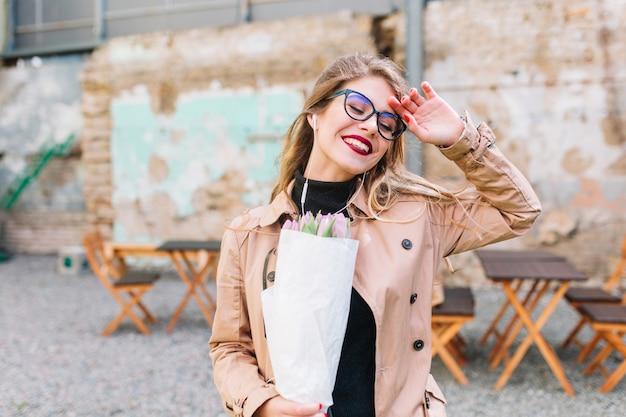 Fröhliches glückliches mädchen mit lila tulpen kam nach einem anstrengenden tag ins café. hübsche junge frau, die ihren geburtstag im straßencafé feiert, hat einen blumenstrauß als geschenk erhalten. dating im restaurant