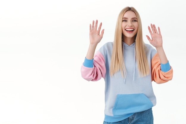 Fröhliches, gut aussehendes blondes mädchen im hoodie, das zum abschied oder hallo mit beiden händen winkt